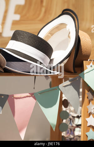 Summer straw hats in a decorated festive shop window. Beautiful vintage hats sale stall at a market - Stock Photo