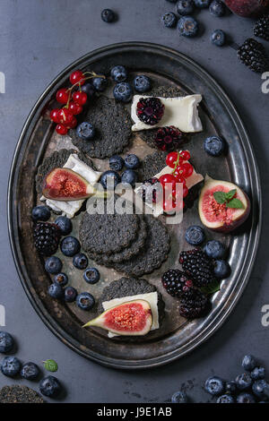 Black crackers with cheese and berries - Stock Photo