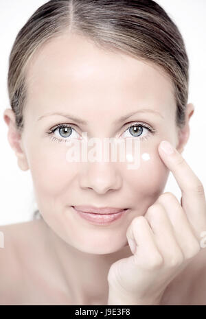 Young woman with cream under eyes - Stock Photo