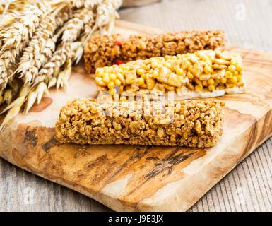Granola or muesli bars on wooden board , whole wheat protein snacks - Stock Photo