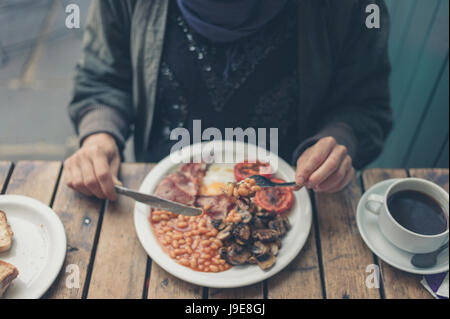 A young woman is having a traditional english breakfast - Stock Photo