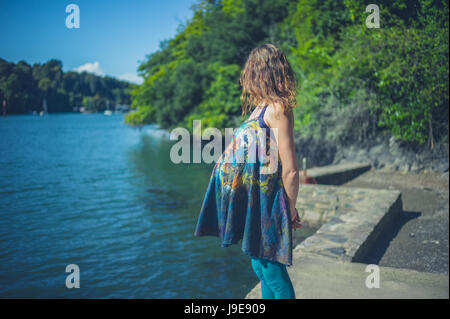 A young pregnant woman is standing by the river in a forest on a sunny day of summer - Stock Photo
