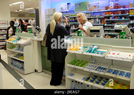 A woman customer talking to a shop assistant at the checkout counter of a Boots the Chemist pharmacy drugs store - Stock Photo