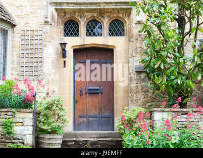 Old dark brown wooden doors in limestone cottage surrounded by flowers and plants . - Stock Photo