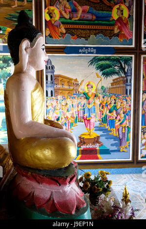 Buddha effigy in front of a painted mural depicting scenes from the life of the Buddha in Phnom Sambok temple near - Stock Photo
