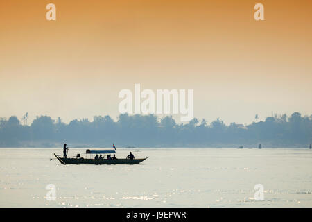 Tourist boat on the Mekong river looking for Irrawaddy River Dolphins near Kratie - Stock Photo