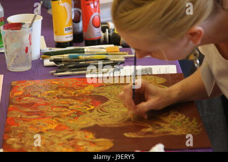 Female artist painting on canvas in studio - Stock Photo