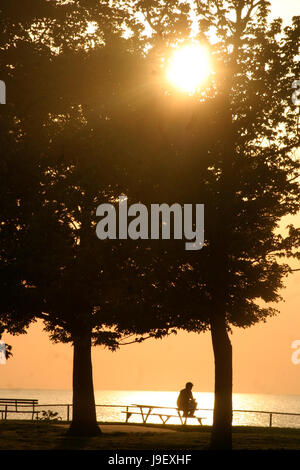 Man alone on bench by the lake at sunset - Stock Photo