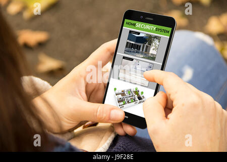 security video concept: woman holding a 3d generated smartphone with cctv app on the screen. Graphics on screen - Stock Photo