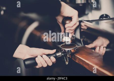 Coffee making, pressing ground coffee in portafilter - Stock Photo