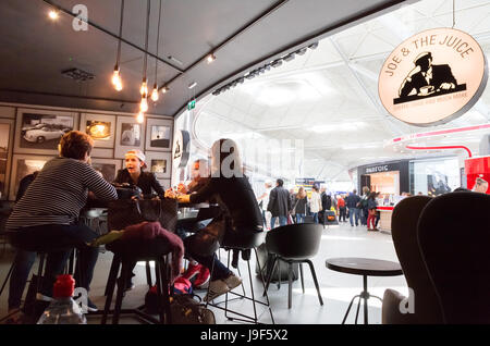 People drinking at the Joe & the Juice cafe, Stansted airport departures lounge, London UK - Stock Photo