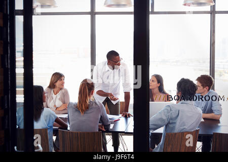Man stands to address colleagues at a meeting in a boardroom - Stock Photo