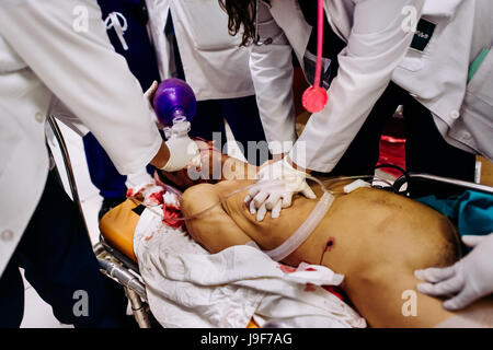 Emergency physicians provide a cardiopulmonary resuscitation to a young gang member, with an abdominal gunshot wound, - Stock Photo
