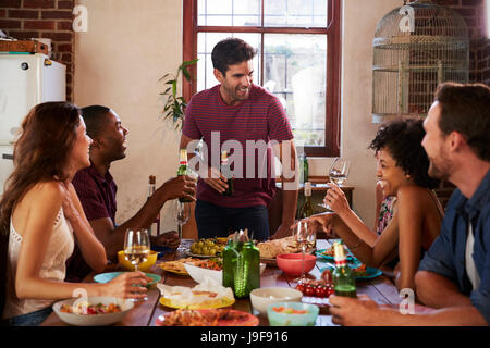 Friends with drinks at the table during a dinner party - Stock Photo