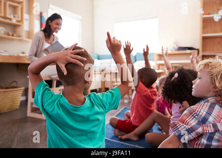 Pupils At Montessori School Raising Hands To Answer Question - Stock Photo