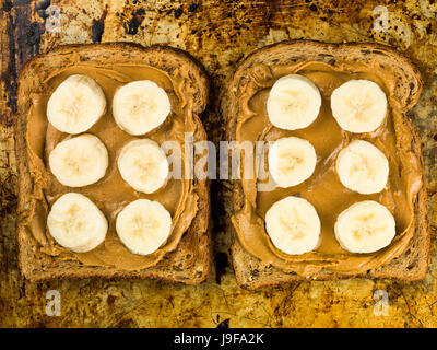 Sliced Banana and Peanut Butter on Wholegrain Toast On An Oven Tray - Stock Photo
