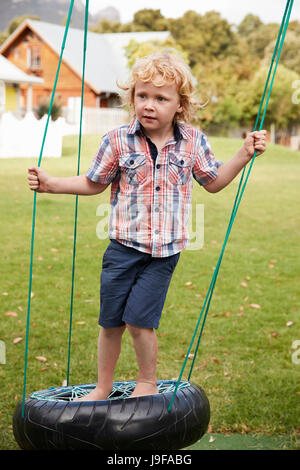Children At Montessori School Playing On Swings During Break - Stock Photo