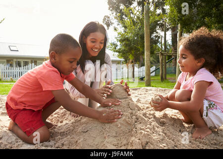 Teacher At Montessori School Playing With Children In Sand Pit - Stock Photo