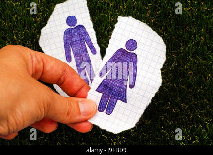 Person hand holding piece of paper with hand drawn woman figure. Other piece of paper with drawn man figure on grass - Stock Photo