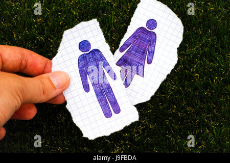 Person fingers holding piece of paper with hand drawn man figure. Other piece of paper with drawn woman figure on - Stock Photo