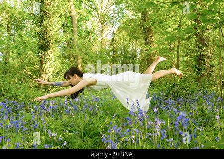Young woman levitating amongst bluebell flowers in British woodland - Stock Photo
