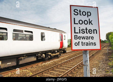 Stop Look Listen Beware of Trains sign on the edge of train tracks in rural norfolk as the diesel train passes - Stock Photo