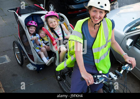 Woman cyclist on bike / bicycle with + 3 children; Co Pilot child seat with helmet & towing cycle Chariot trailer with two / 2 kids with helmets. UK.