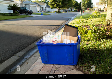 A blue coloured recycling box containg plastics and paper products on the sidewalk of a residential housing estate - Stock Photo