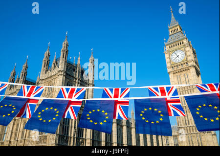European Union and United Kingdom flag Brexit bunting hanging together in front of Big Ben and the Houses of Parliament - Stock Photo