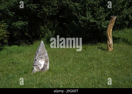 Stone figures on green grass near trees on a summer day - Stock Photo