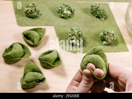 Green Tortelloni. Typical Bolognese homemade fresh stuffed pasta in the preparation process at the moment of closing. - Stock Photo