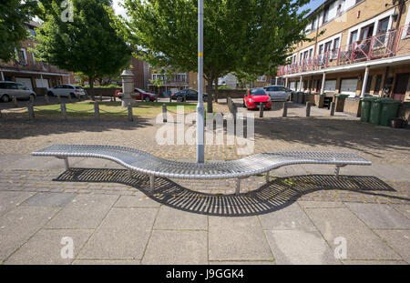 Curved stainless steel bench at base of lamp post near housing, Rotherhithe, London, UK - Stock Photo
