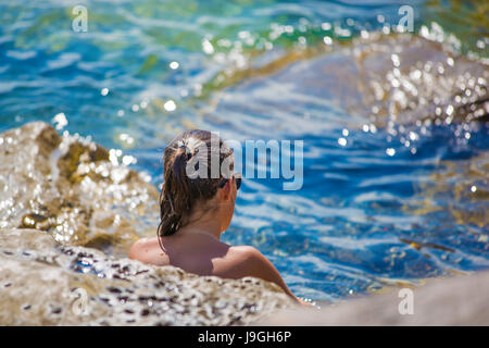 Young beautiful woman resting or taking sun bath on the rocky beach. Mediterranean sea, could be in Italy, Greece, - Stock Photo