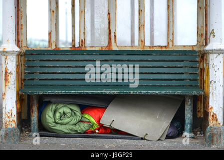 Homelessness. Homeless person's bedding stored under a bench in a bus stop. - Stock Photo