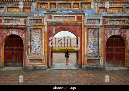 Tourist at Cua Tho Chi gate, historic Hue Citadel (Imperial City), Hue, North Central Coast, Vietnam (MR) - Stock Photo