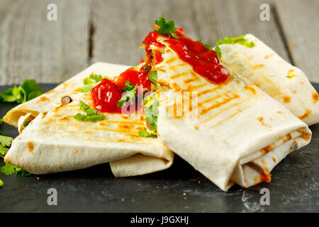 Vegetarian burritos wraps with beans, avocado and cheese on a slate. Love for a healthy vegan food concept - Stock Photo