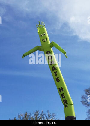 Donate Here inflatable cute cartoon character dancing against blue sky - Stock Photo
