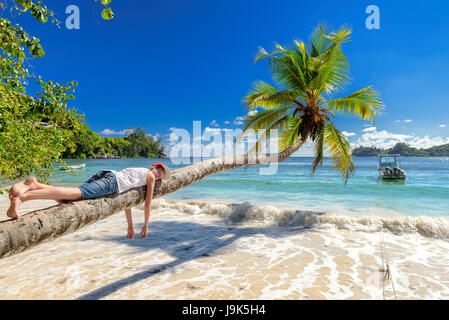 Cute boy resting lying on a palm tree at tropical island on vacationю - Stock Photo