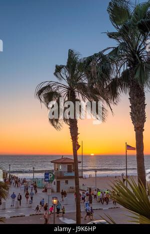 People walk along the promenade on Manhattan Beach at sunset, Los Angeles. California. - Stock Photo