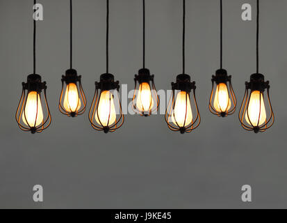 Beautiful hanging light bulbs on plain background for card, banner, wallpaper - Stock Photo