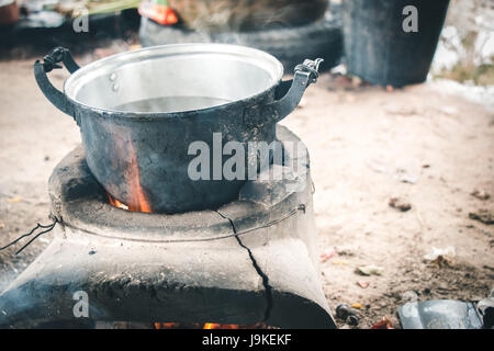 old aluminium pot on stove. water is boiling for cook in hut at the countryside. local and vintage cooking lifestyle. - Stock Photo