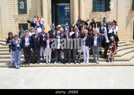 Tour group photo of carnival organisers on steps of Auberge de Castille palace in city centre of Valletta, Malta - Stock Photo