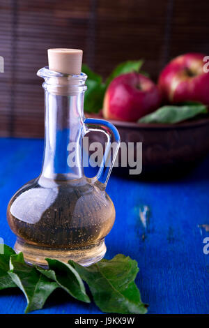Apple cider vinegar in glass bottle on blue background. Red apples in brown bowl - Stock Photo