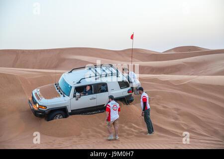 Car stuck on sand whilst off-roading in Dubai, United Arab Emirates - Stock Photo