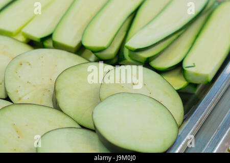 Fresh zucchini sliced on the counter of the kitchen. Vegetables for cooking. - Stock Photo