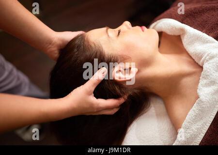 woman having head massage at spa - Stock Photo