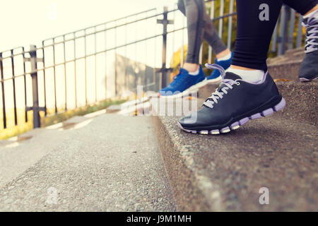 close up of feet running downstairs in city - Stock Photo