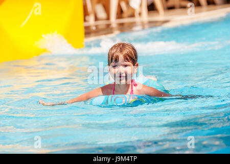 Little girl in a swimming tube playing in a pool in water - Swimming pool girl christmas vacation ...