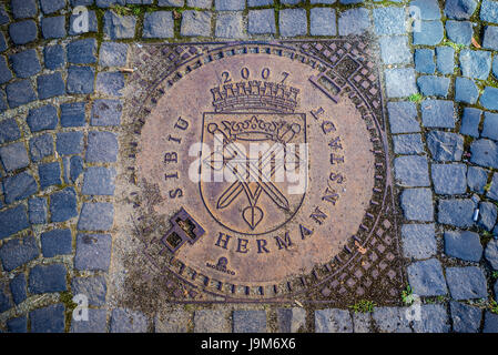 Manhole cover celebrating European Capital of Culture 2007 award on a Strada Cetatii (Castle or Fortress Street) - Stock Photo