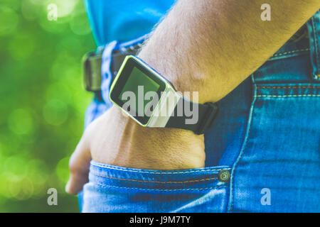 Close up shoot of male hand in jeans pocket and wearing smart watch with blank screen. - Stock Photo